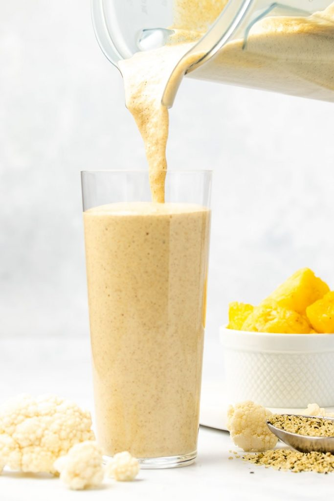 Cauliflower smoothie being poured from a blender into a glass, surrounded by cauliflower florets, hemp hearts and a white bowl of diced pineapple