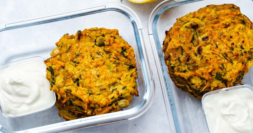 zucchini carrot fritters in 2 glass meal prep containers with a side of greek yogurt