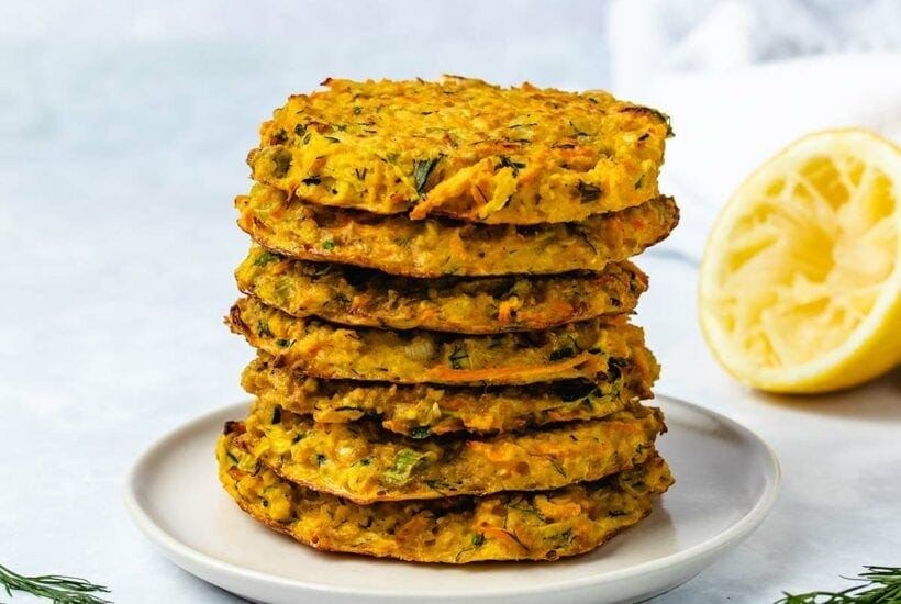 A stack of 7 zucchini carrot fritters on a cream coloured plate next to dill garnish and half a squeezed lemon