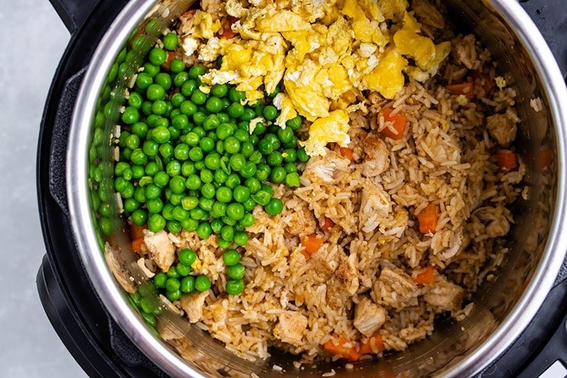 Peas and scrambled egg being added to cooked rice, chicken and carrots in an Instant Pot