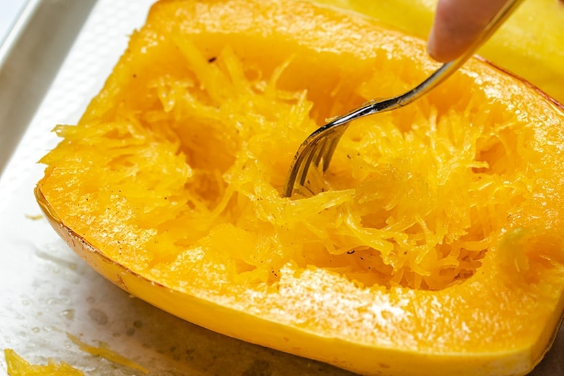 roasted spaghetti squash being scraped out of the skin using a fork