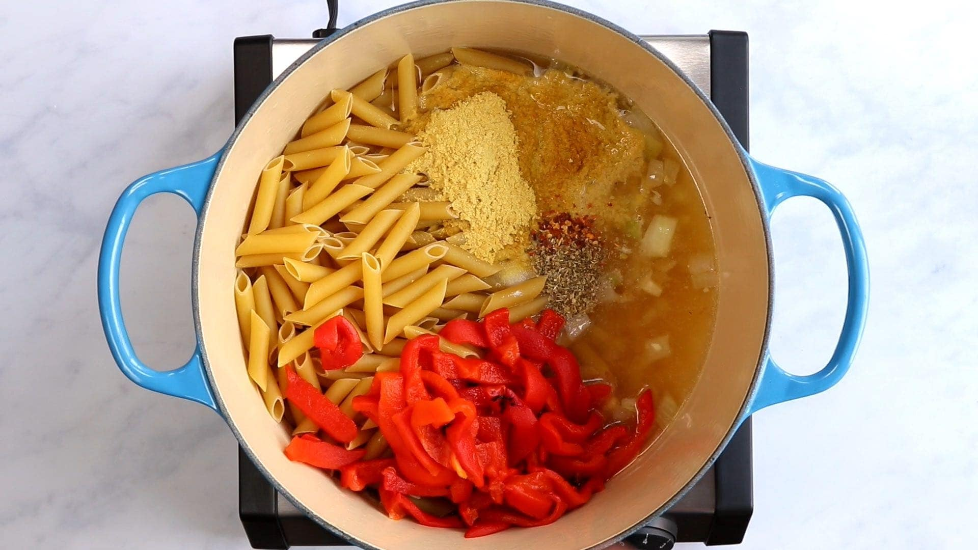 penne, roasted red pepper, nutritional yeast, spices, onion and broth in a blue dutch oven