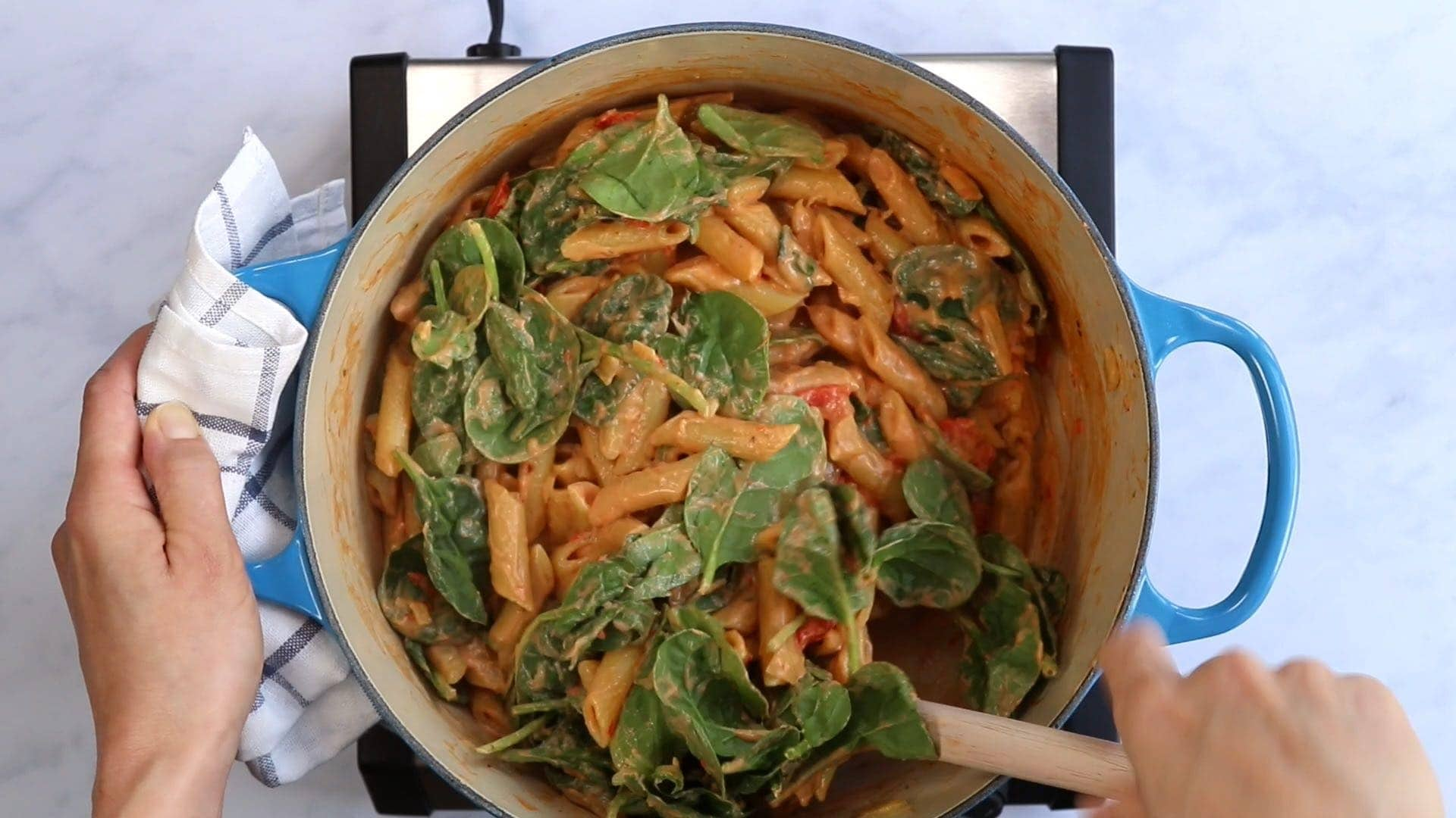 stirring spinach into penne with creamy cashew sauce in a blue dutch oven