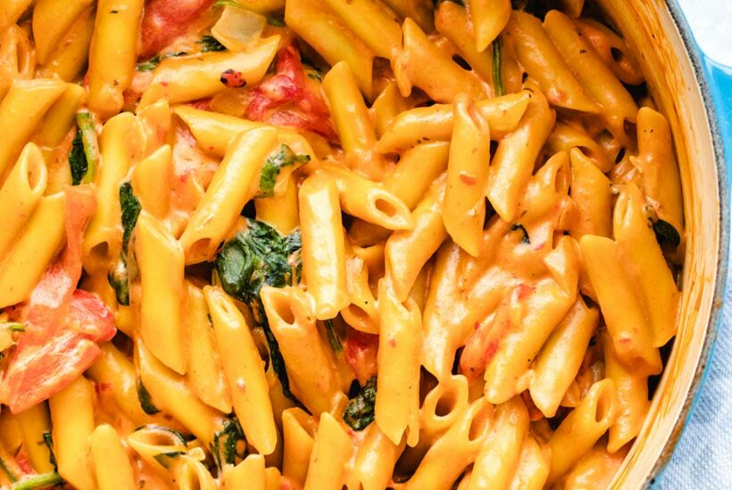 Creamy vegan one pot pasta with roasted red peppers and spinach in a blue dutch oven