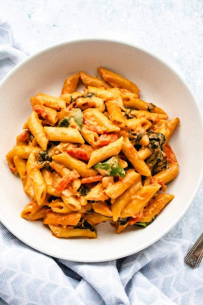 Creamy vegan one pot pasta with roasted red peppers and spinach on a white plate next to a blue linen