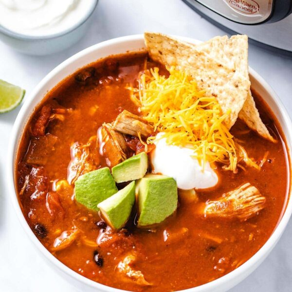 chicken enchilada soup in a white bowl garnished with diced avocado, sour cream, grated cheese and corn chips, sitting in front of an Instant Pot