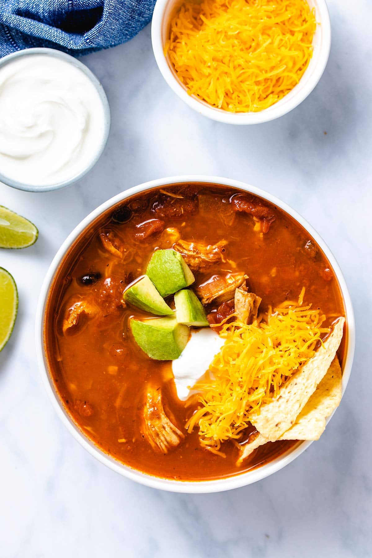 chicken enchilada soup in a white bowl garnished with diced avocado, sour cream, grated cheese and corn chips next to lime wedges and small bowls of grated cheese and sour cream