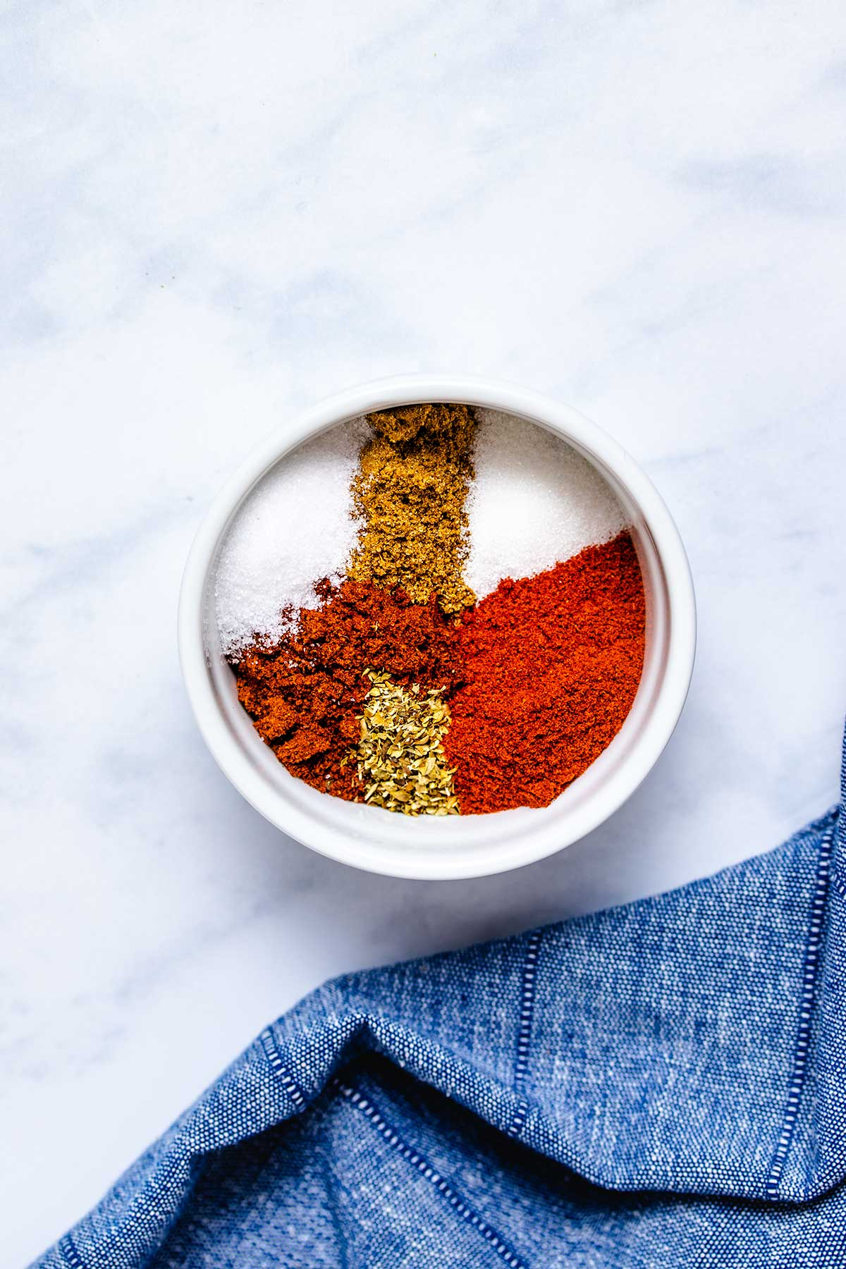 Chili powder, smoked paprika, cumin, oregano, salt and sugar in a small white bowl next to a denim linen