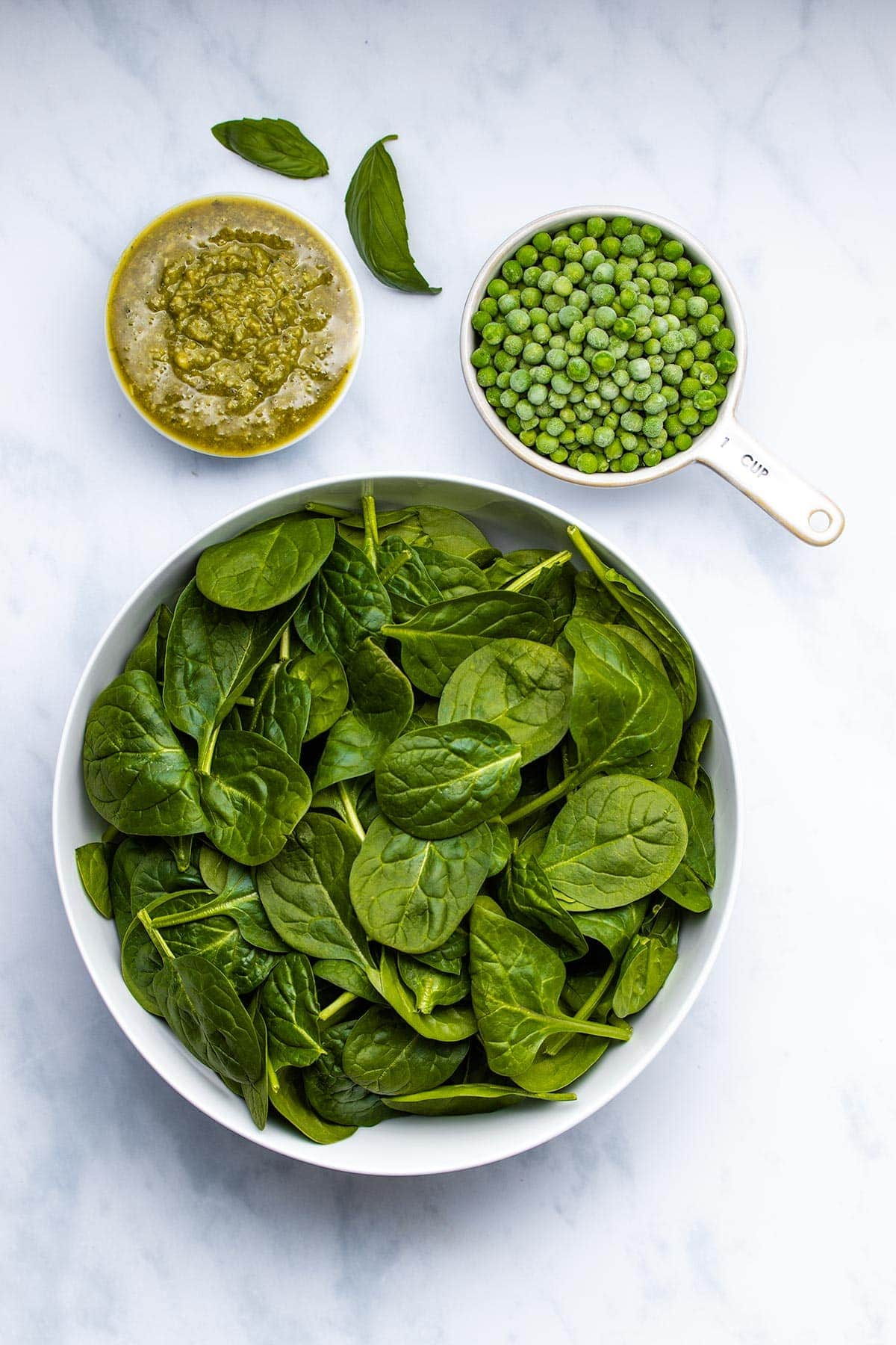 pesto, frozen peas and baby spinach in white bowls viewed from overhead