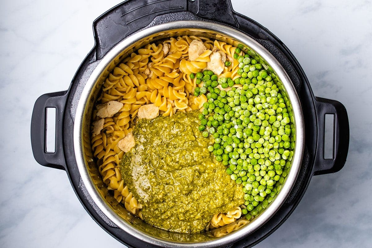 pesto and frozen peas layered on top of cooked rotini and chicken in an Instant Pot