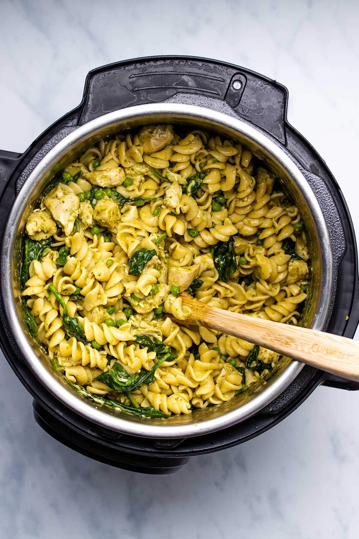 pesto chicken pasta in an Instant Pot with a wooden spoon inserted