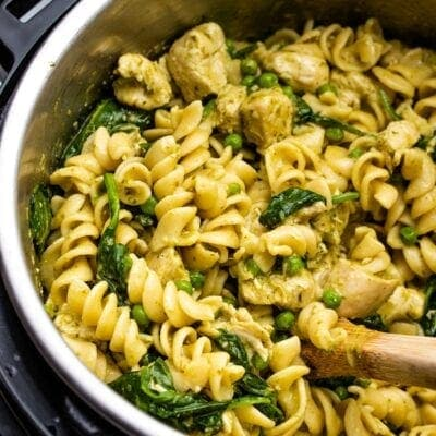 pesto chicken pasta in an Instant Pot being scooped by a wooden spoon