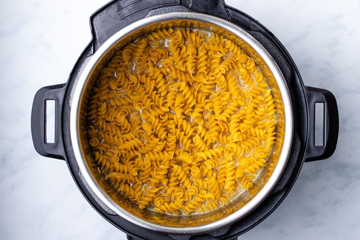 uncooked rotini on top of chicken and broth in an Instant Pot