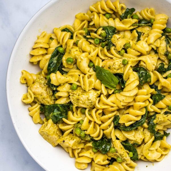 pesto chicken pasta in a white bowl viewed from overhead