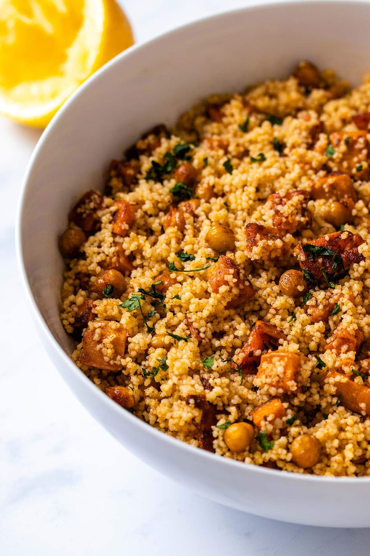 moroccan couscous in a white bowl with a squeezed lemon in the background