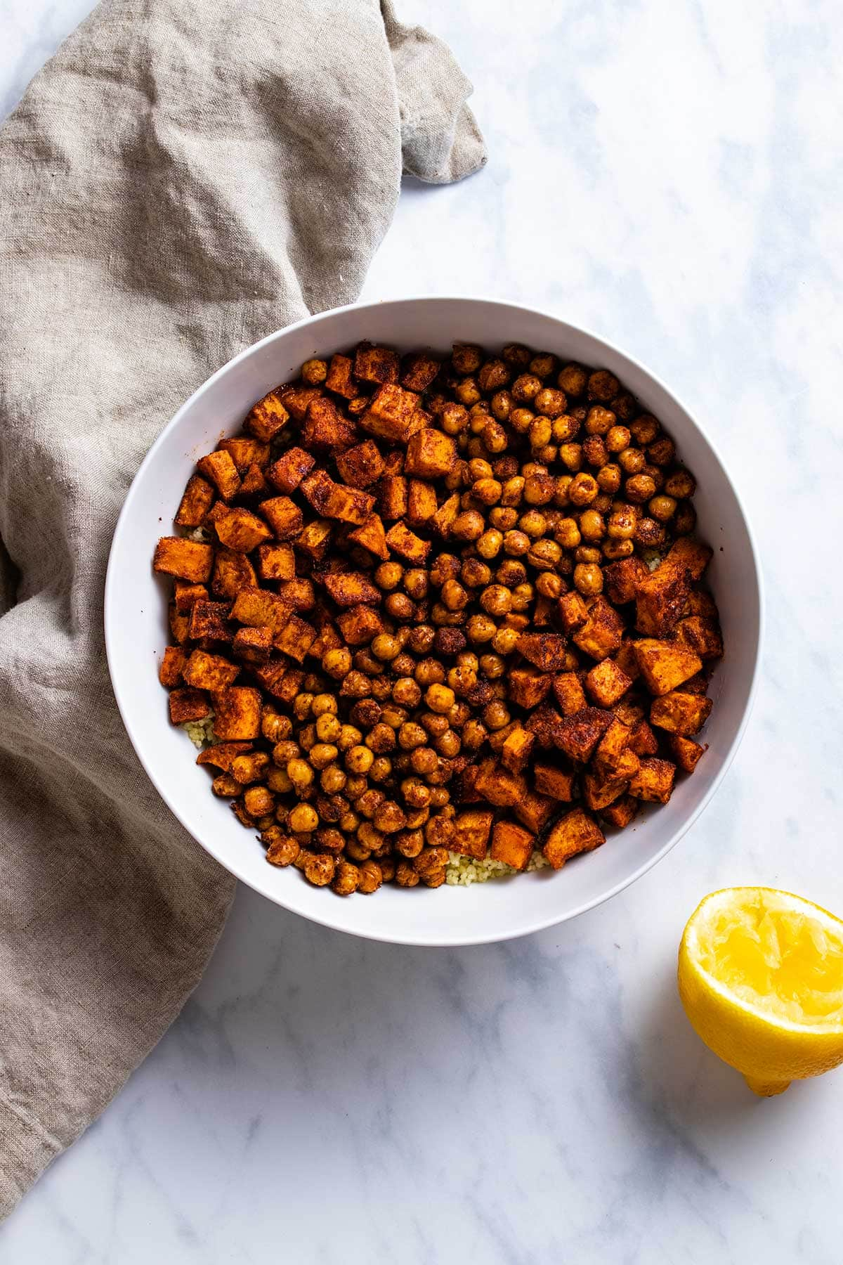 roasted chickpeas and diced sweet potato covered in moroccan spices on top of couscous in a white bowl next to a brown linen and half a lemon