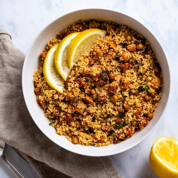 moroccan couscous in a white bowl garnished with 3 lemon slices next to a light brown linen and squeezed lemon