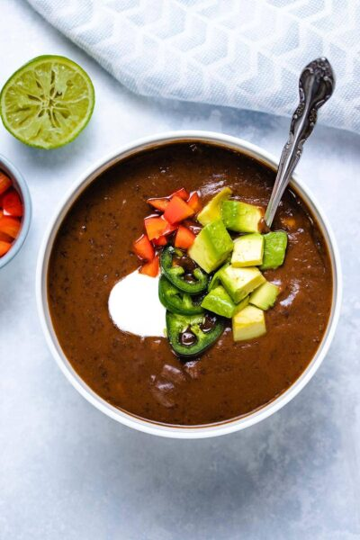 black bean soup in a white bowl garnished with sour cream, sliced jalapeno, diced red pepper and diced avocado, with a spoon inserted