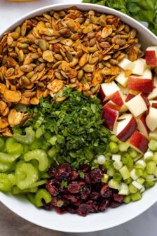 diced apple, sliced green onion, dried cranberries, chopped parsley, diced celery, roasted almond and pumpkin seeds in a white bowl viewed from overhead, next to a mason jar of dressing