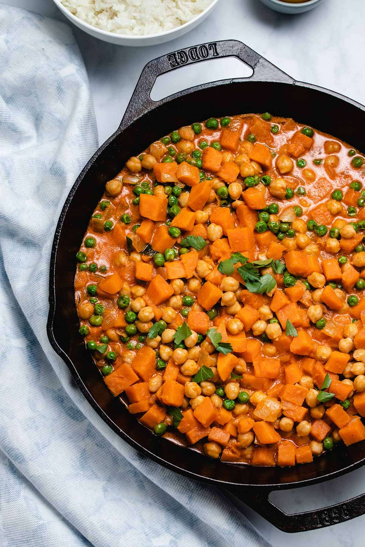 Sweet Potato Chickpea Coconut Curry in a cast iron skillet next to a blue linen and rice in a white bowl