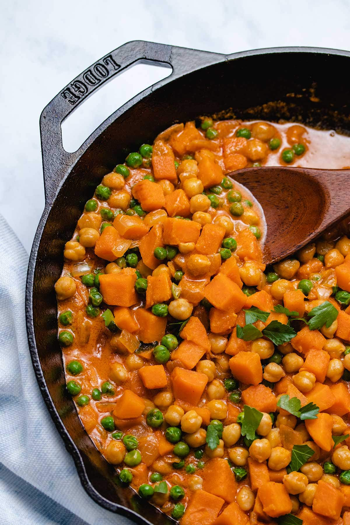 Sweet Potato Chickpea Coconut Curry in a cast iron skillet being scooped by a wooden spoon