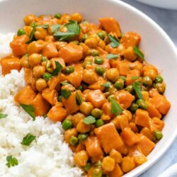 Sweet potato chickpea coconut curry served with jasmine rice in a shallow white bowl next to a blue linen