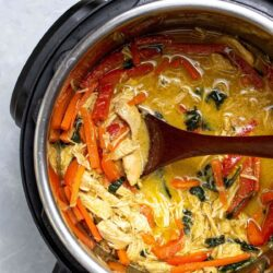 Thai chicken curry in an Instant Pot being scooped with a wooden spoon