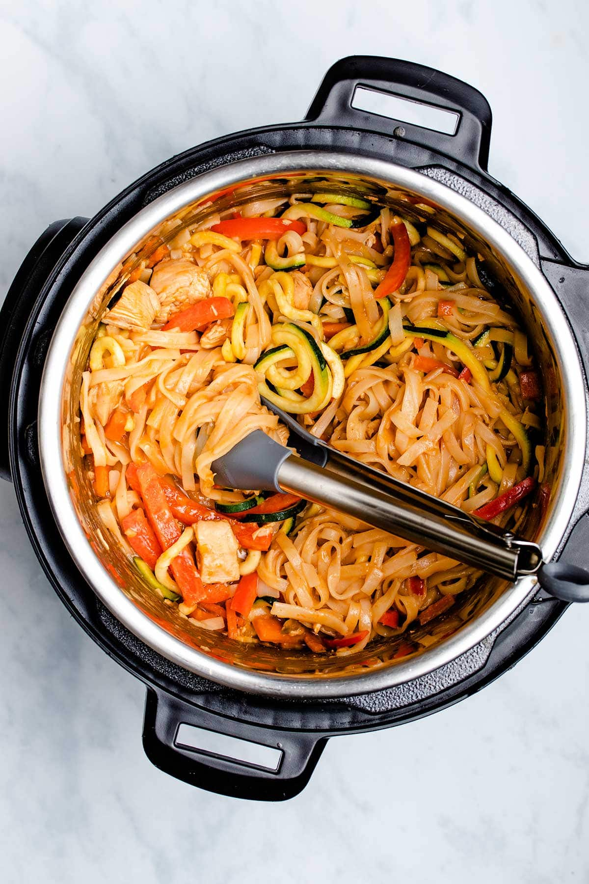Chicken Pad Thai in an Instant Pot being swirled with kitchen tongs