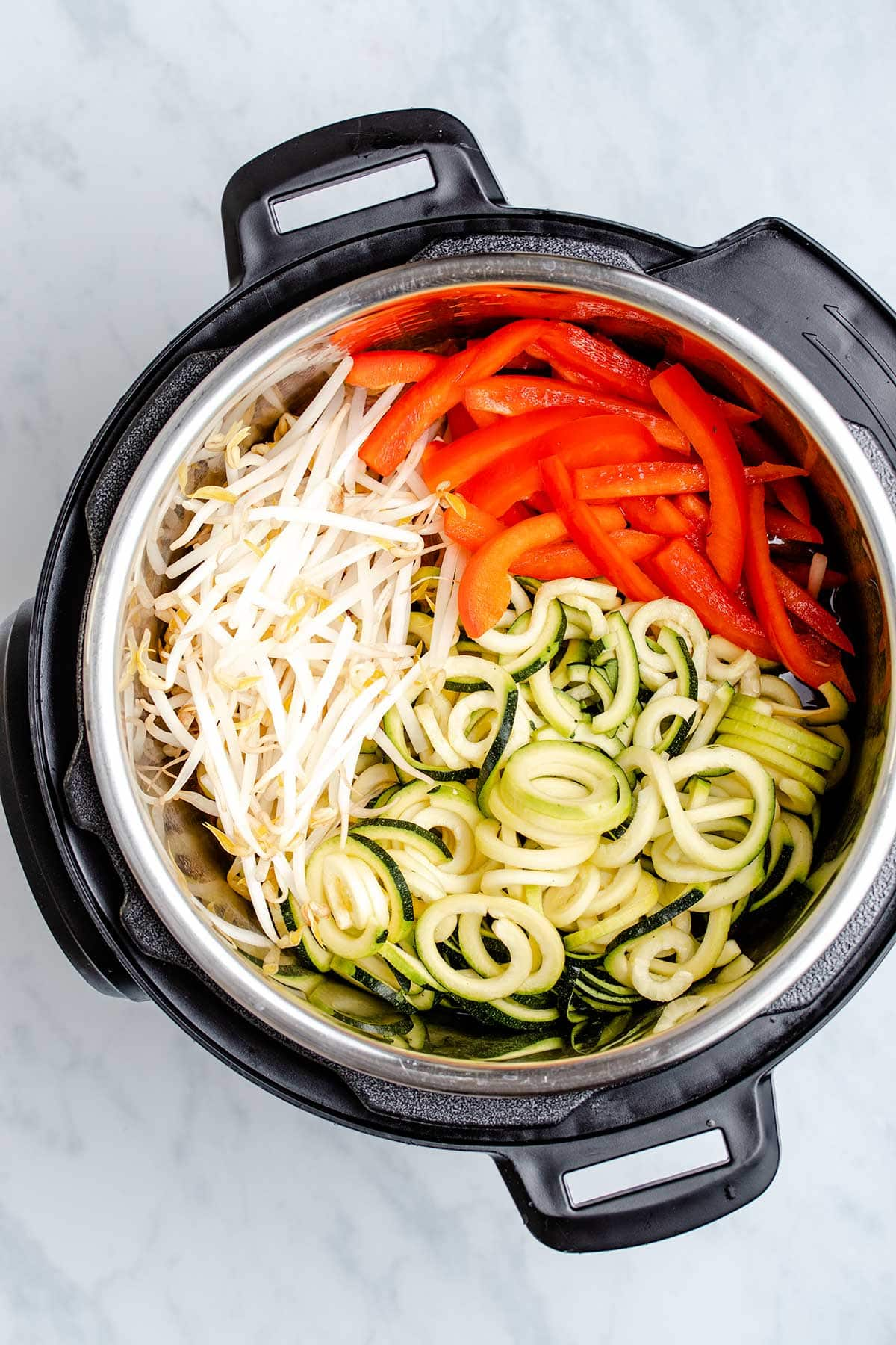 sliced red bell pepper, bean sprouts and spiralized zucchini in an Instant Pot viewed from overhead