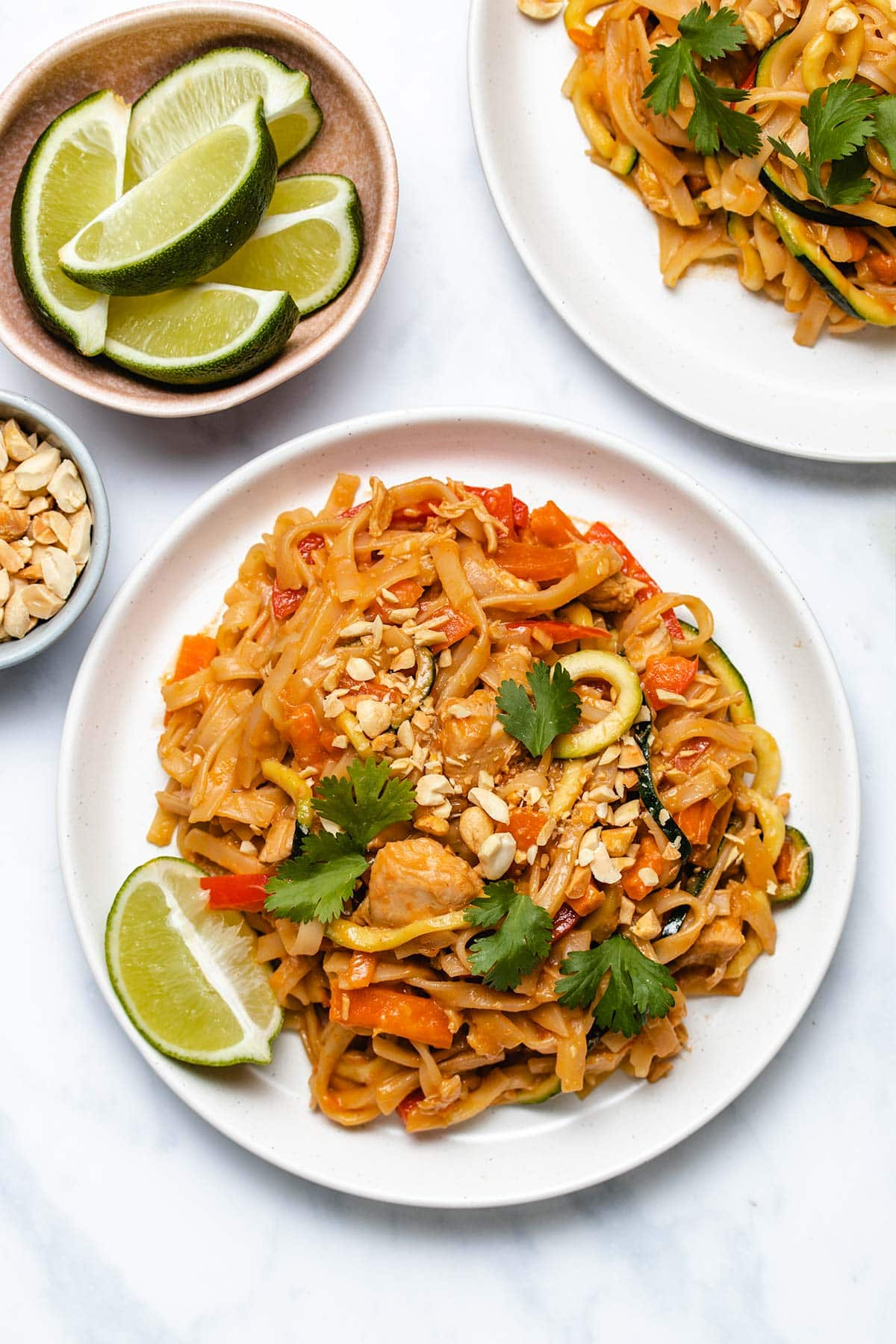 Instant Pot Chicken Pad Thai on a white plate garnished with cilantro and chopped peanut, next to small bowls of garnish and a second plate