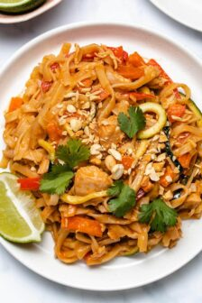 Instant Pot Chicken Pad Thai on a white plate garnished with cilantro, chopped peanuts and a lime wedge