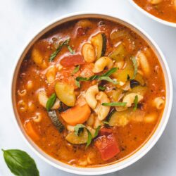 Instant Pot Vegetable Soup in a white bowl next to a small bowl of basil garnish