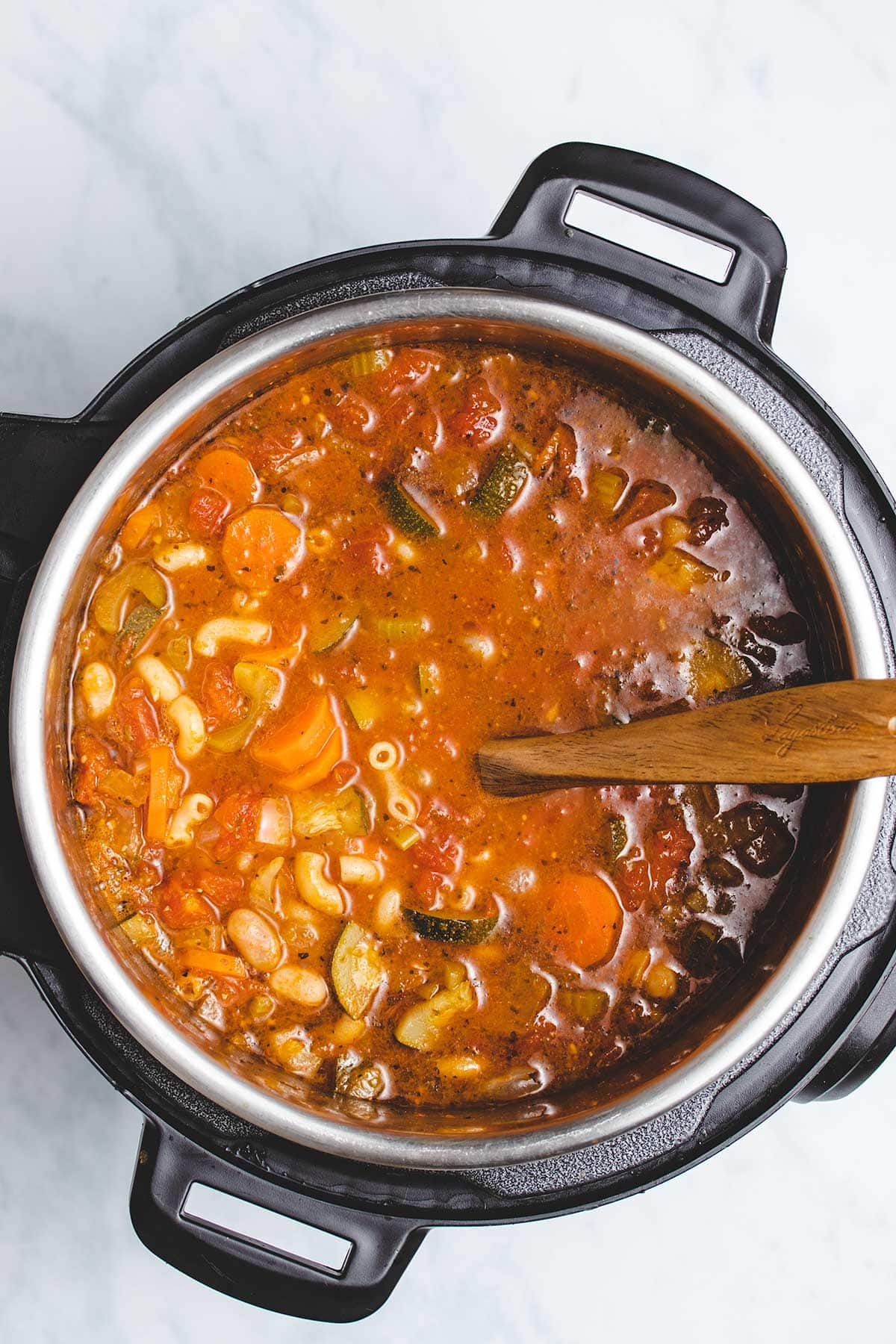 Vegetable Soup in an Instant Pot being stirred by a wooden spoon
