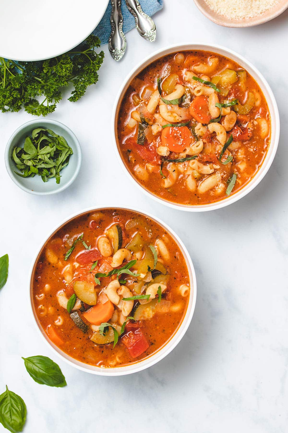 Instant Pot Vegetable Soup in two white bowls garnished with fresh basil and parmesan