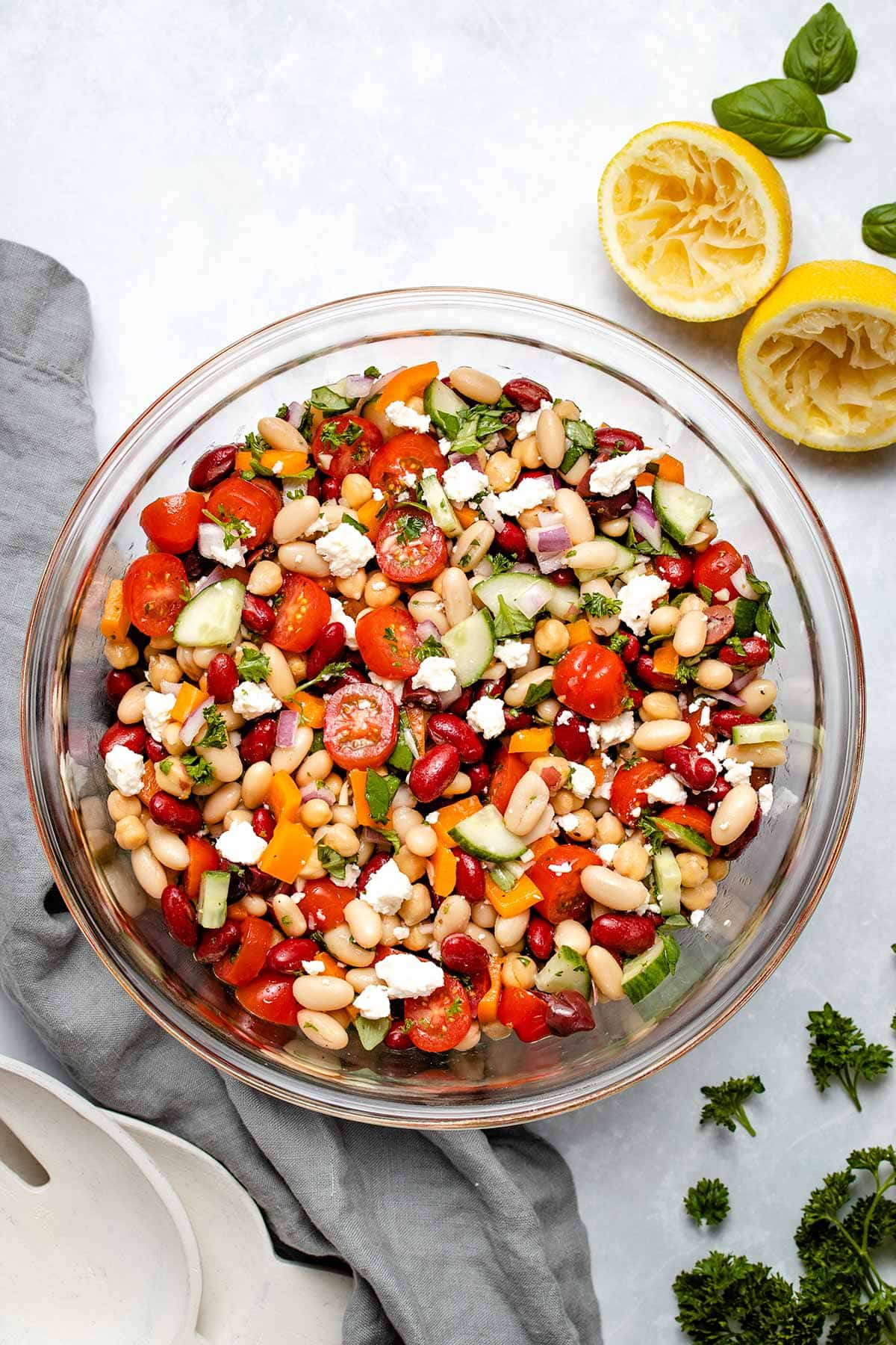 Mediterranean Bean Salad in a glass bowl next to a grey linen and squeezed lemon halves