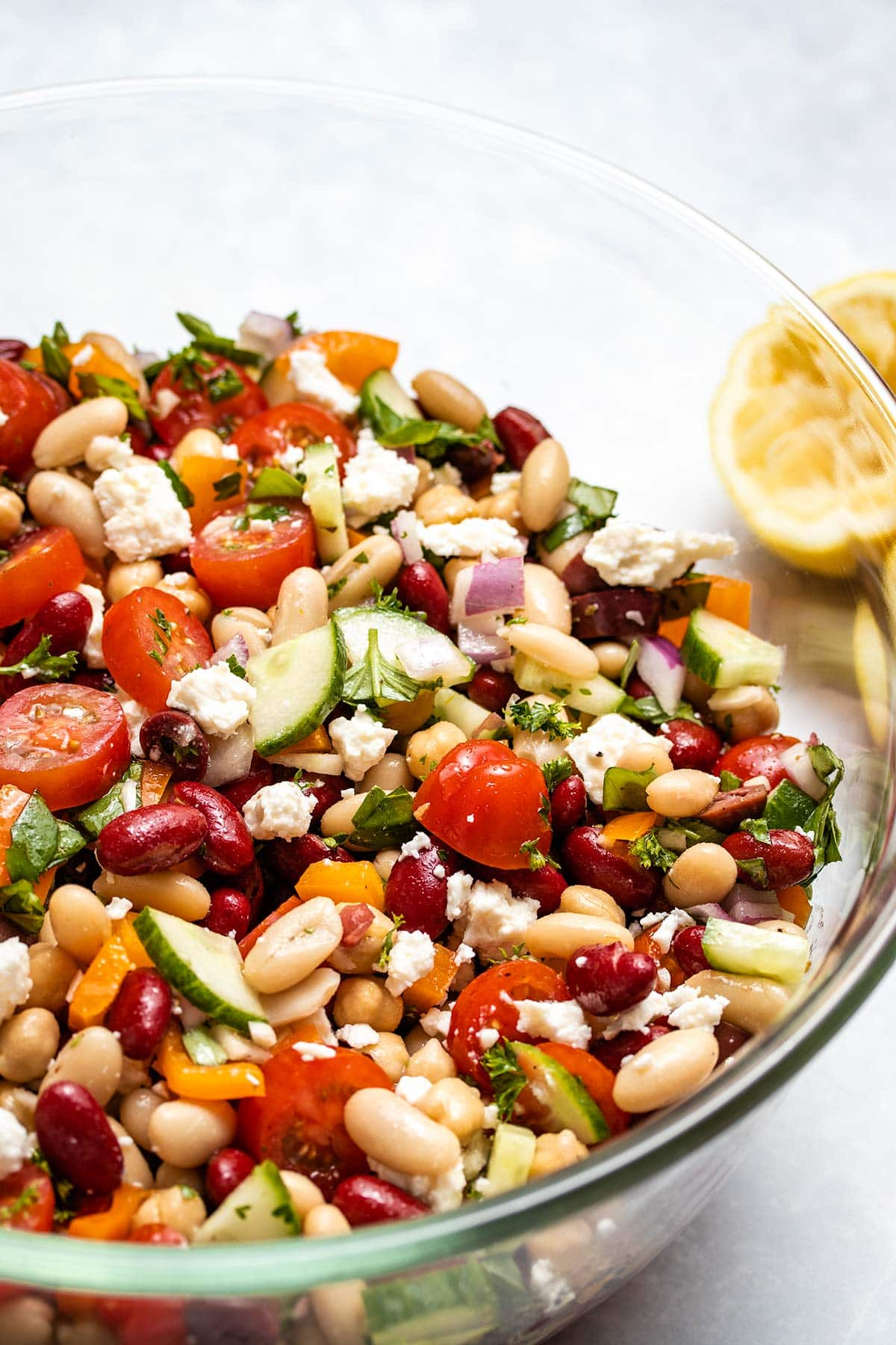 A closeup of Mediterranean Bean Salad in a glass bowl with lemon halves in the background
