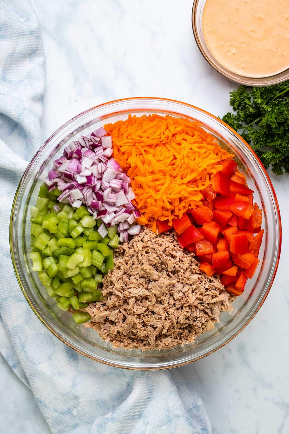 Cooked tuna, diced celery, diced red pepper and grated carrot in a glass bowl next to a blue linen and a bowl of dressing