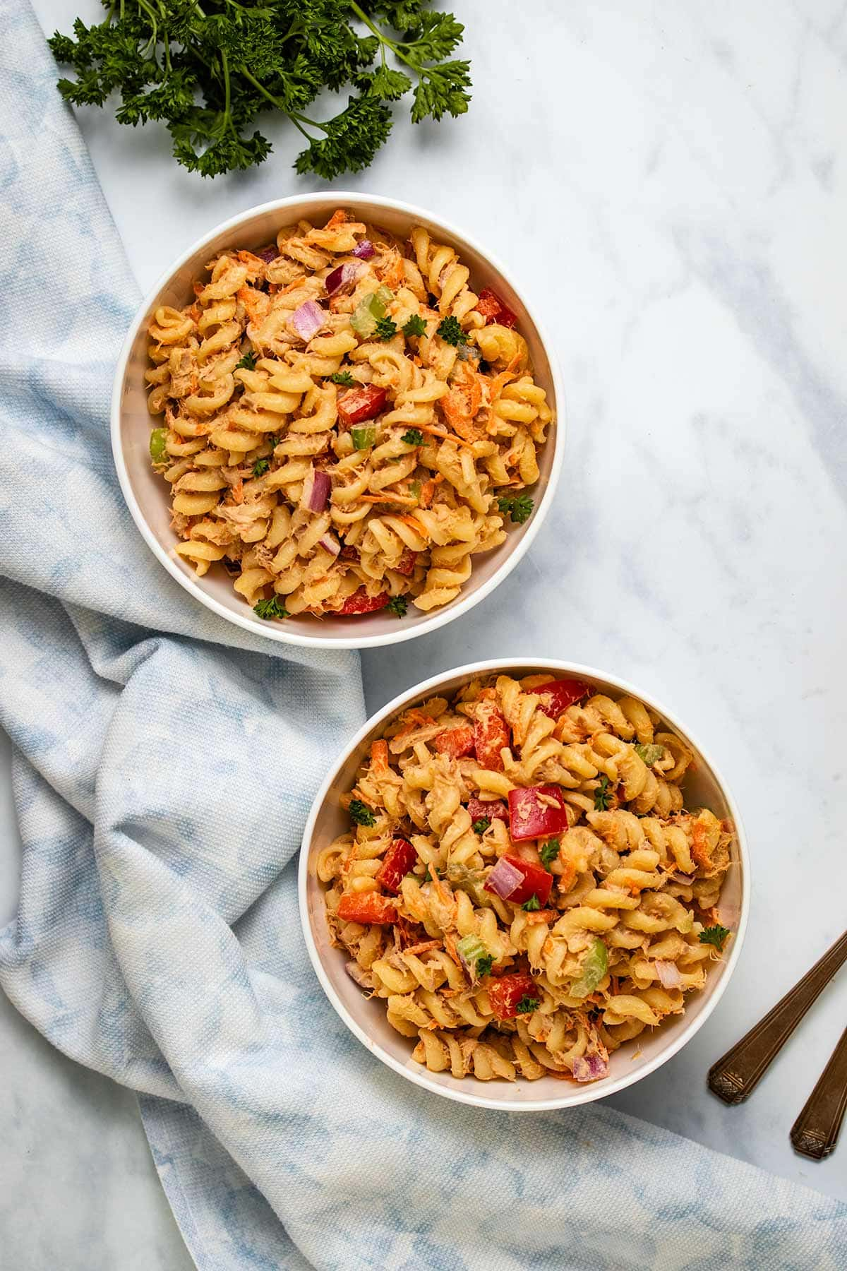 Spicy Tuna Pasta Salad in two white bowls next to a blue linen and parsley
