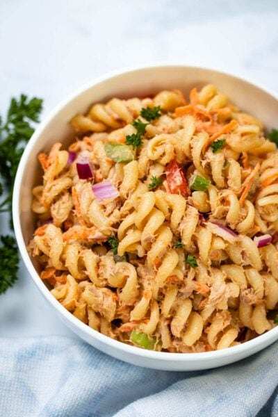A closeup of Spicy Tuna Pasta Salad in a white bowl next to a blue linen