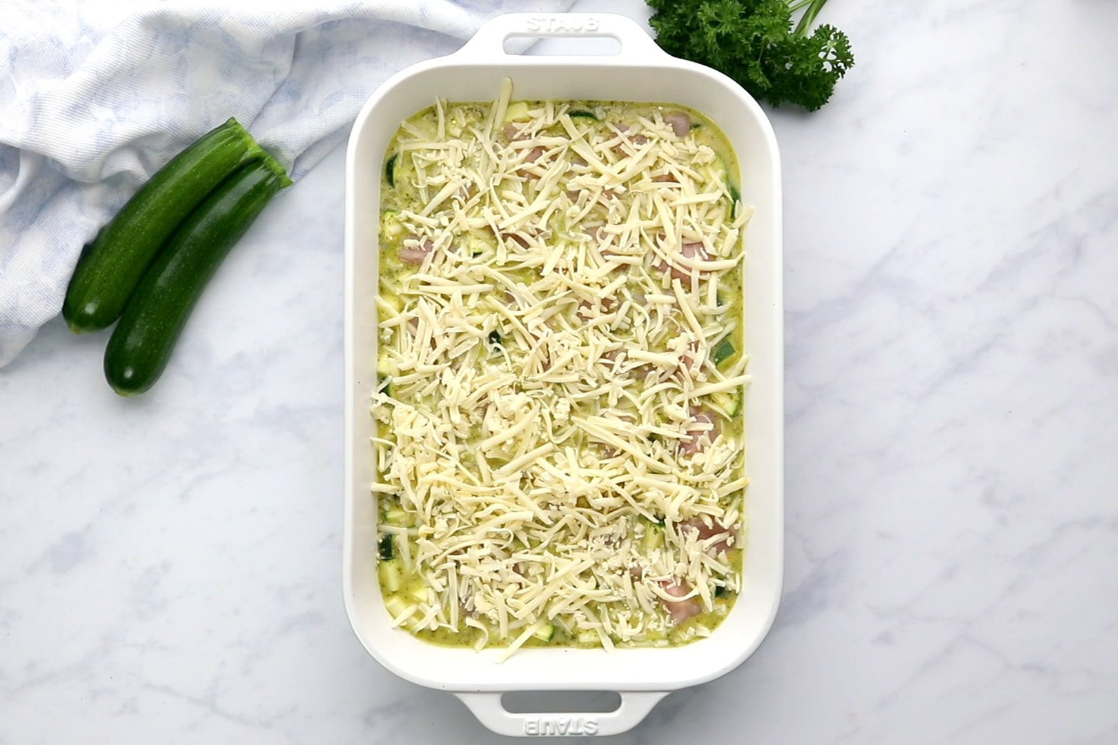 uncooked chicken and zucchini casserole in a rectangular white dish