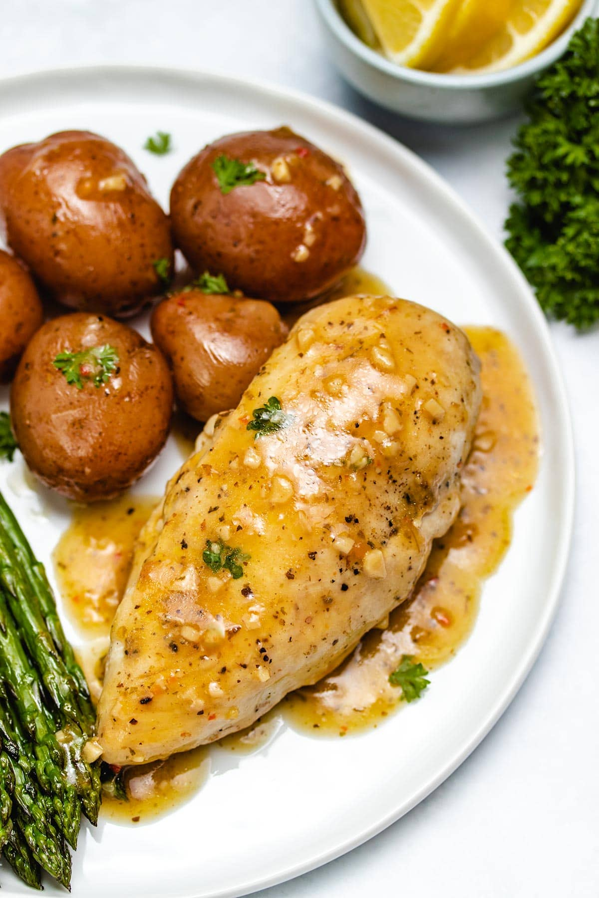 Chicken and potatoes with lemon garlic sauce and asparagus on a white plate