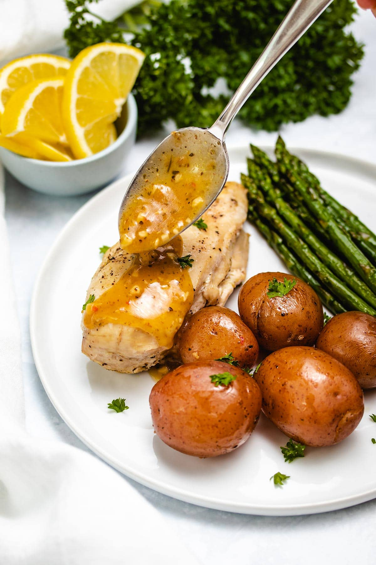 spooning lemon garlic sauce onto a chicken breast that is on a white plate with potatoes and asparagus