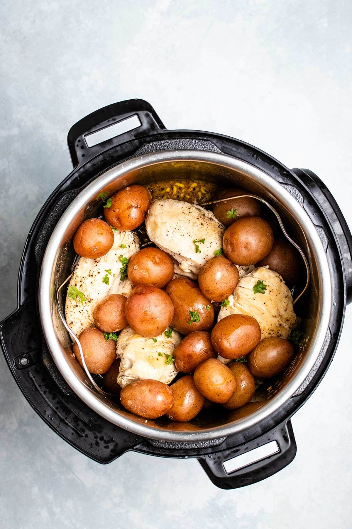 chicken and potatoes sprinkled with fresh parsley in an Instant Pot
