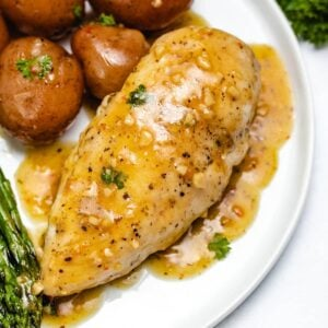 a chicken breast with lemon garlic sauce next to potatoes and asparagus on a white plate