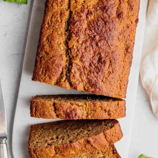 A loaf of almond flour zucchini bread being sliced on a marble serving tray