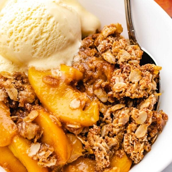 Peach Crisp in a white bowl with a scoop of vanilla ice cream and a spoon tucked in
