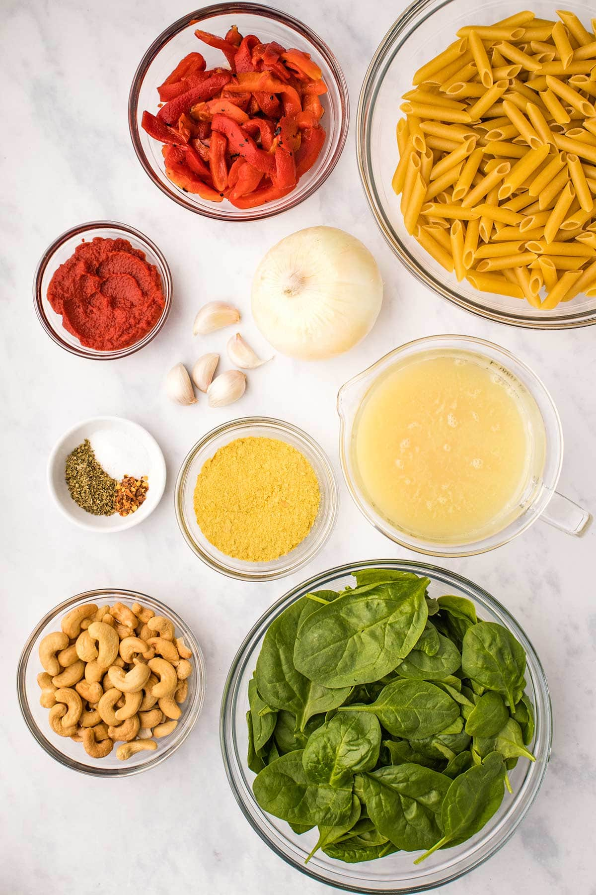 Ingredients needed to make creamy Instant Pot Vegan Pasta in glass bowls viewed from overhead