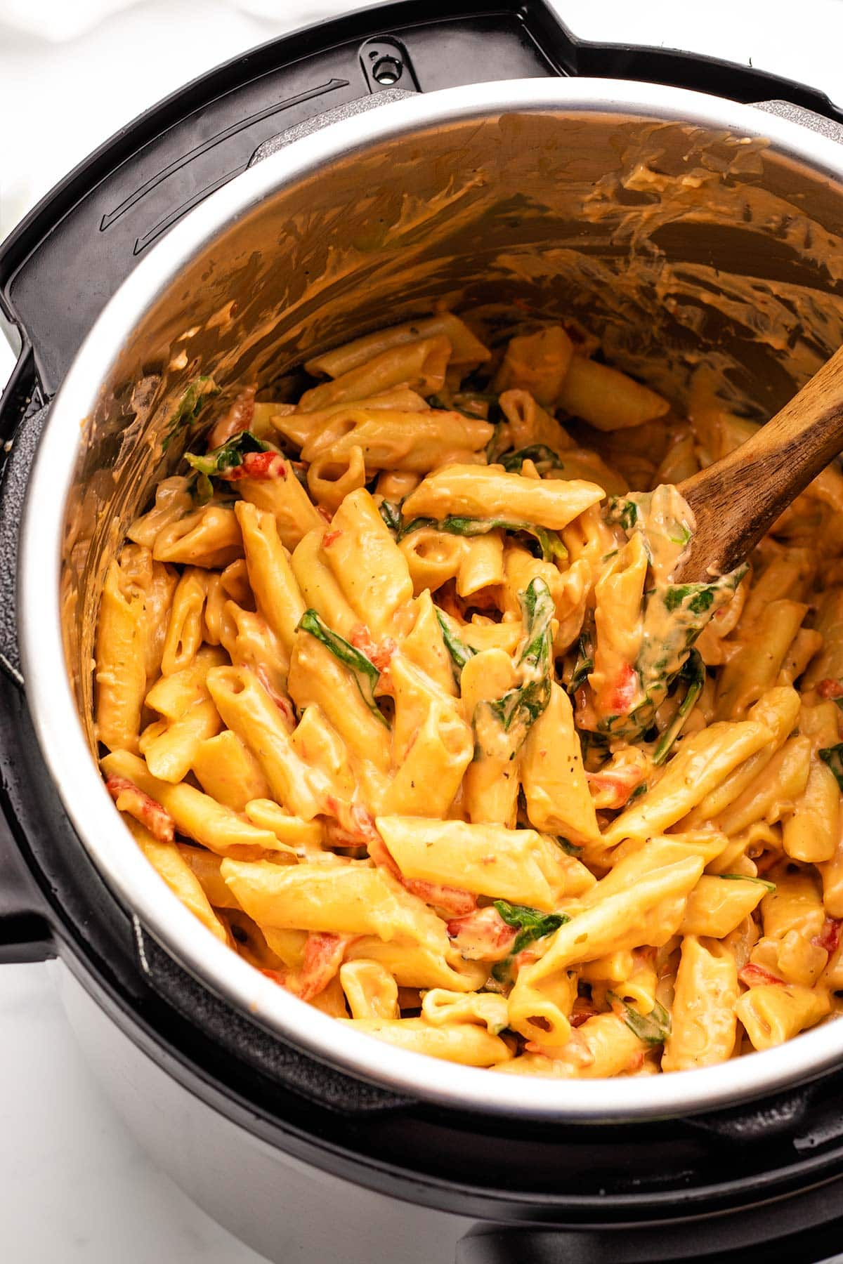 creamy vegan pasta with spinach and roasted red peppers being stirred by a wooden spoon in an Instant Pot