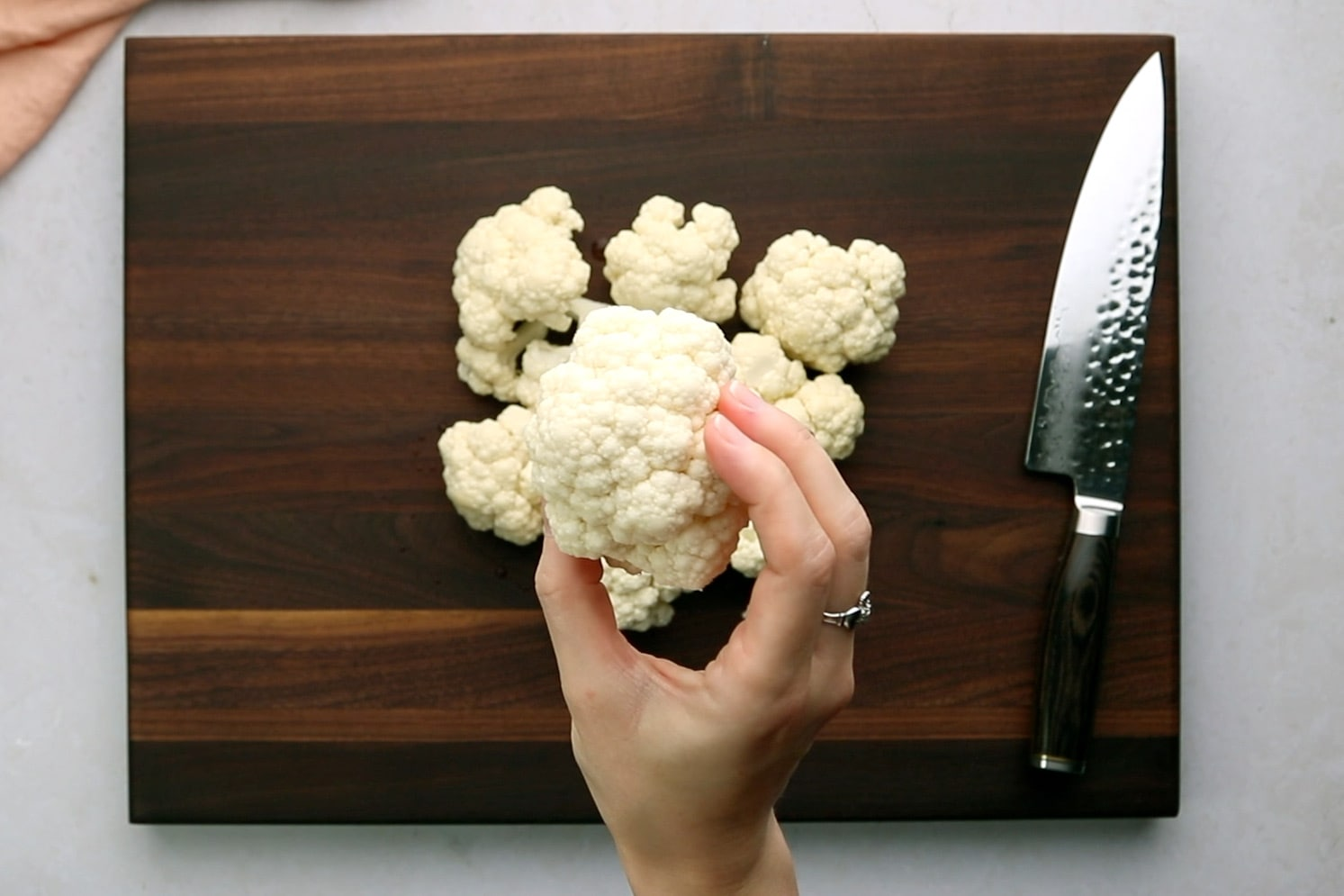 Holding a large cauliflower floret over a wooden cutting board.