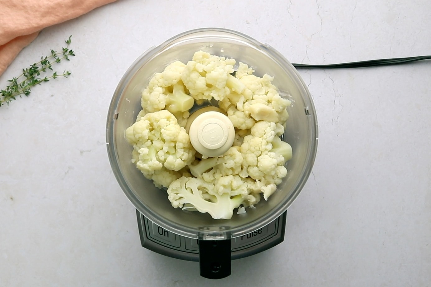 Cooked cauliflower and garlic in a food processor viewed from overhead.